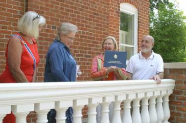 "Nebraska State Regent, Judy Ekeler, and Lewis-Clark Chapter Regent, Mabel Petet, present a certificate to Patty Manhart, former May Museum Director and Jeff Kappeler, new museum director, celebrating the DAR grant given to the Dodge County Historical Society to rebuild the May Museum's porch, on which they are standing. Patty Manhart said, ""Receiving these funds meant so much coming from DAR, a wonderful national historical organization."""