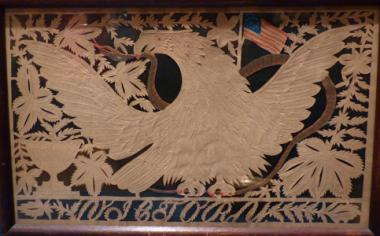 "In the twenty-first century, we marvel at these intricate hand-cut pictures, called papyrotamia, but in 19th-century America, many had mastered this skill. The bald eagle with widespread wings has long been one of the most revered patriotic images. Here with the nation's flag in the background, the eagle grasps a snake in his beak. The letters across the lower border spell ""VICTORY."""