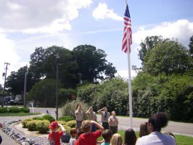 Boy Scouts raise the American Flag at the dedication ceremony of the installation of a flag pole at the Parent Child Development Corporation Day Care Center in West Point, Va. The PCDC approached the Old St. John's Chapter because they wanted a flag pole and flag on their property to instill patriotism in the children and teach them flag etiquette.