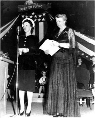 Marie Francis Woolcott joined the NSDAR in 1933, and served as a page at Continental Congress in Washington D C on two separate occasions, once as the State Regent's personal page. She was honored for 65 years of service to the organization 1998 and died in 2001 as an original member of the Jonas Babcock Chapter. Marie Francis was the War Finance Director for the State of Washington for WWII and raised thousands and thousands of dollars for the cause. She is shown here at a war bond rally in Seattle with El