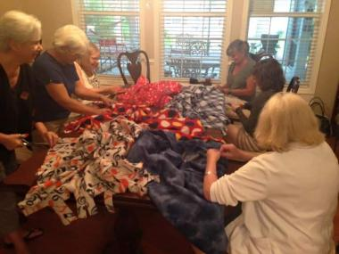 Several tables just like this one of Emily Geiger chapter South Carolina members making lap robes for a local veterans home for National Day of Service.