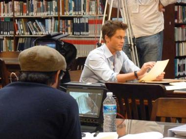 Rob Lowe examining one of the documents containing information about his ancestor.