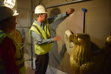 A Project Superintendant from Christman Co. shows the President General an example of how the neutral toned paint colors will make the newly painted white eagles contrast from the wall.