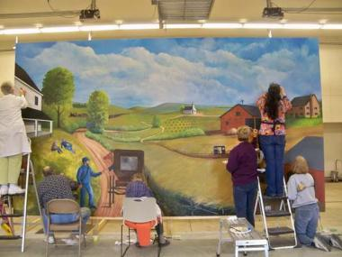 Alana Speckman, Eleanor Boston, and Jackie Gillespie, members of the Battle Creek Chapter, Michigan, have been involved with the painting, development and completion of three murals in the Convis Township Hall in Calhoun County, Michigan. Each mural is 9½ by 16½ feet and tells the history of the township. The first begins with the early settlers to the region in the early 1800s. It reflects the friendships and interactions of the settlers with Native Americans. The second mural is the period 1860 to 1920 an