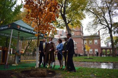 Special guests at the ceremonial tree planting stand in the shadow of historic Independence Hall with the newest addition to the park.