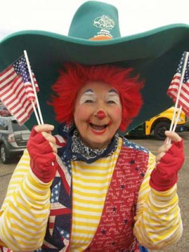 "Marsha Berland, a member of the Cactus Wren Chapter, Arizona, is a professional clown and often volunteers her time. Her alter ego, ""Marshmellow,"" is a very patriotic clown dressed in red, white and blue and carries U.S. Flags when she is in parades. As she is also the literacy chair for her chapter, she tries to incorporate an element of reading in her message to children. This photo was taken when she was ""clowning"" at the Phoenix School for Homeless Children."