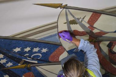 A conservator carefully touches up the canvas mural.