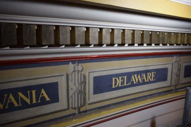 The paint work around the state names that was chipping and fading prior to being painted white during the restoration to take back to the original neutral color scheme of the Hall.
