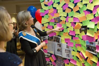 President General Lynn Young reads some of the many volunteer stories posted by Daughters from around the world on the Celebrate America! Wall.