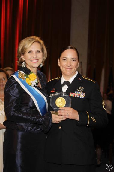 President General Lynn Young presents the Margaret Cochran Corbin Award to Staff Sergeant Julia A. Stalker, a flight medic who received the Distinguished Flying Cross for the extraordinary courage she displayed during the course of a 60-hour rescue mission in the jungle of Afghanistan in late June 2011.