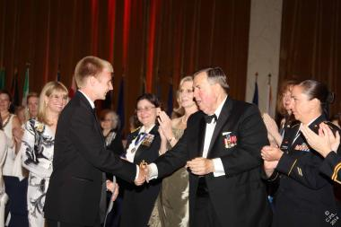 General Mick Kicklighter, who addressed the audience on the efforts of the Vietnam War Commemoration, congratulates the National Outstanding Youth Volunteer winner, Mitchel Wirth, for his commitment to veterans.