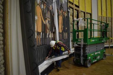 The original mural tapestries were designed by artist and architect James Monroe Hewlett and depicted scenes from four important cities of colonial times – Boston, New York, Philadelphia and Charleston. Here you can see the screen installer cutting away excess material after he has positioned the fabric in place over the panels.
